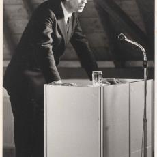 L. de Vries van Makrotest tijdens zijn lezing op de opening van de Ploeg-toonzaal in Heemstede - Pictura (fotografie), onbekend