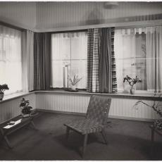 Beursstand ingericht als woonkamer met gestreepte Ploeg-gordijnen - Pictura (fotografie), Ed van der Elsken (Amsterdam)
