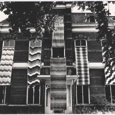 Bedrukte gordijnstoffen, waaronder 'Damon', hangend uit de vensters van een oud vervallen pand - Paul de Nooijer, Pictura (fotografie)