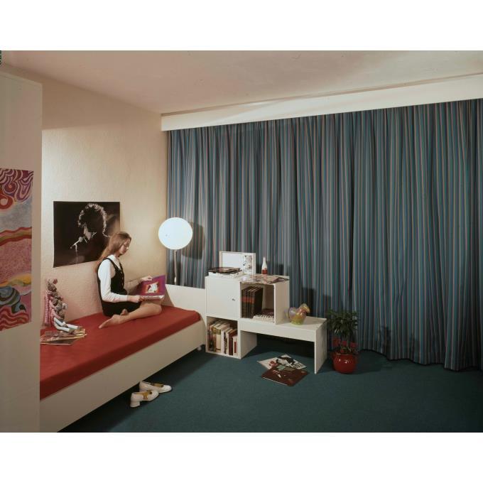 Model poserend op (slaap) bank in slaapkamer met Bob Dylan poster
