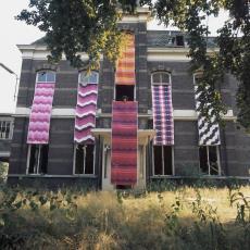 Kleurrijke gordijnstoffen hangend vanuit de vensters van een vermoedelijk oud vervallen pand - Pictura (fotografie), Paul de Nooijer