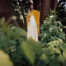 Model buiten poserend bij boom in geelwitte jurk van kledingstof 'Ranuncula' - Urs (Luzern Marty, Pictura (fotografie)