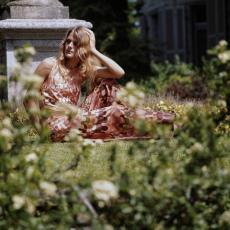 Zittend model in bruine lange jurk van kledingstof 'Agrimonia' poserend in tuin - Pictura (fotografie), Urs (Luzern Marty