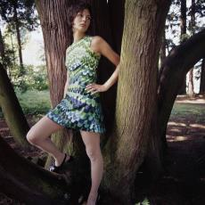 Model poserend voor boom in korte groen/blauwe jurk van kledingstof 'Agrimonia' - Pictura (fotografie), Urs (Luzern Marty