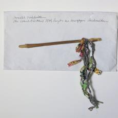Enveloppe met stokje waaraan een proefje met lussen en knopen van textiel - Lange, Tommy de, Textielmuseum (registratiefoto), Désirée Scholten-van de Rivière
