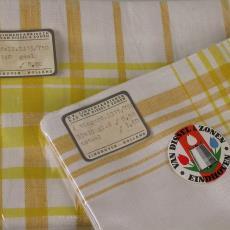 Tafellaken en vingerdoekjes 'Ruitdessin geel' (dessinnr.750) in cellofaanzakjes - Linnenfabrieken E.J.F. van Dissel & Zonen (Eindhoven), Textielmuseum (registratiefoto), Kitty van der Mijll Dekker (Fischer-)